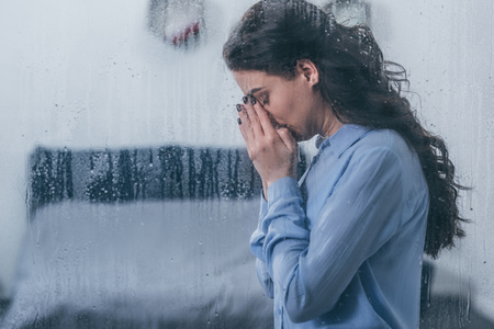Foto de depressed woman covering face with hands and crying at home through window with raindrops and copy space - Imagen libre de derechos