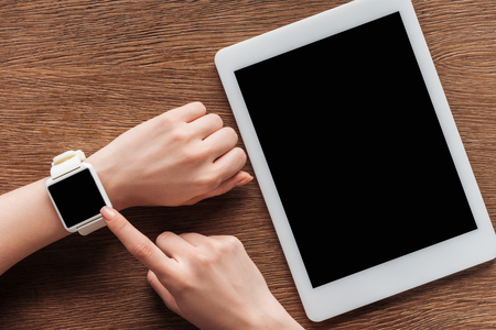 Foto per Partial view of woman with digital tablet and smartwatch with blank screen on wooden background - Immagine Royalty Free
