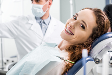 Photo pour selective focus of beautiful woman in braces during examination of teeth near dentist - image libre de droit