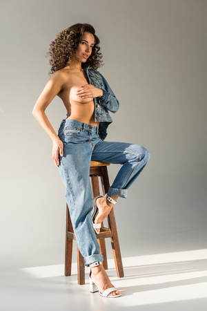 Foto de sexy naked woman covering breast with hand while sitting on chair on grey background - Imagen libre de derechos