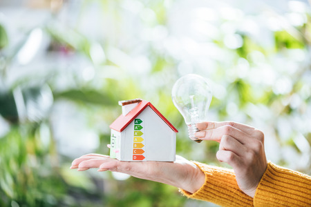 Foto per cropped view of woman holding led lamp and carton house, energy efficiency at home concept - Immagine Royalty Free