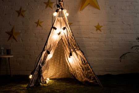Photo for Cozy wigwam with luminous bulbs standing in dak room - Royalty Free Image