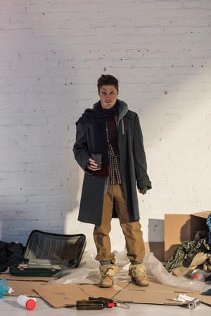Foto de homeless man standing on cardboard and holding disposable cup - Imagen libre de derechos