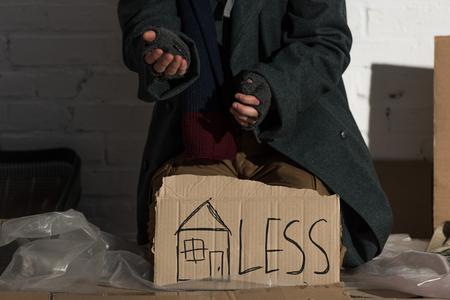 Foto de partial view of begging man with symbol of house and less inscription on cardboard card - Imagen libre de derechos