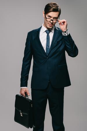 Foto de businessman in suit holding briefcase and touching glasses on grey background - Imagen libre de derechos