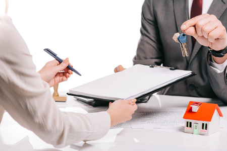 Photo for cropped view of mortgage broker and woman making deal and holding keys isolated on white, mortgage concept - Royalty Free Image