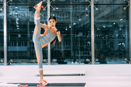 Photo for athletic asian girl in sportswear with leg up standing on fitness mat at gym - Royalty Free Image