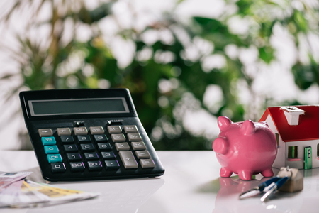 Foto de selective focus of euro banknotes, keys, piggy bank, calculator and house model on white desk, mortgage concept - Imagen libre de derechos