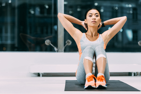 Photo for slim asian sportswoman doing sit-ups on fitness mat at gym - Royalty Free Image