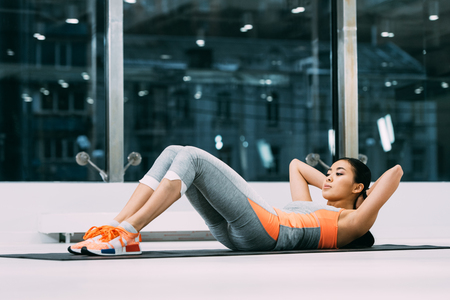 Photo for beautiful asian sportswoman doing sit-ups on fitness mat in sports center - Royalty Free Image