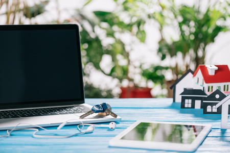 Photo for selective focus of digital tablet, laptop with blank screen and keys near headphones and house model on wooden desk, mortgage concept - Royalty Free Image