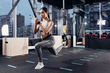 Photo pour athletic asian girl stretching with resistance bands in fitness center - image libre de droit