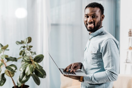 Photo pour african american freelancer smiling and holding laptop - image libre de droit