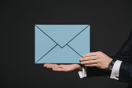 Foto de cropped view of man holding blue envelope isolated on black - Imagen libre de derechos
