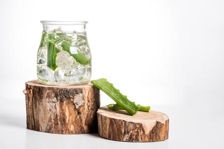 Photo pour Studio shot of glass jar with ice cubes and aloe vera leaves - image libre de droit