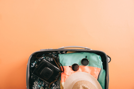 Foto de top view of suitcase with summer accessories and film camera on orange background - Imagen libre de derechos