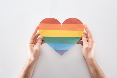 Photo for partial view of man holding paper rainbow colored paper heart on grey background, lgbt concept - Royalty Free Image