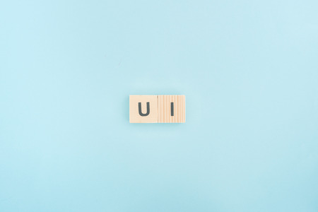 Foto de top view of ui lettering made of wooden cubes on blue background - Imagen libre de derechos