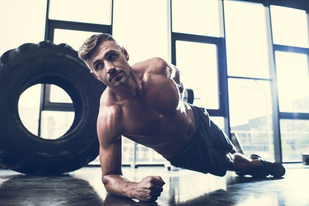 Photo pour handsome shirtless sportsman doing plank on one hand in gym - image libre de droit