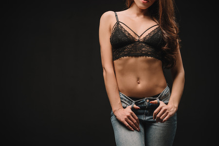 Photo for cropped view of sexy girl posing in lace bra isolated on black - Royalty Free Image