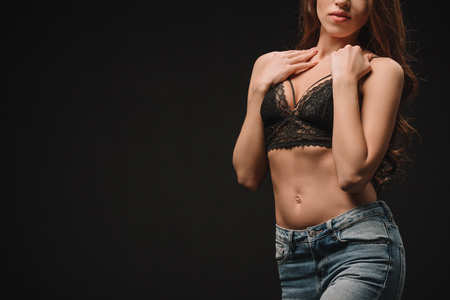 Photo for cropped view of sexual young woman posing in lace bra isolated on black - Royalty Free Image