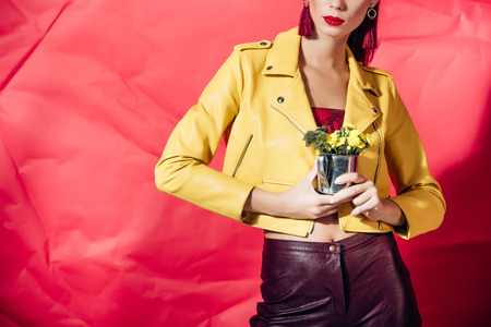 Photo pour cropped view of woman in yellow leather jacket posing with flowers on red background - image libre de droit