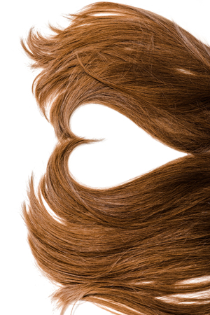 Photo pour cropped view of long brown female hair in shape of heart isolated on white - image libre de droit