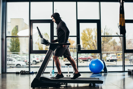 Foto per side view of handsome sportsman in hoodie exercising on treadmill in gym - Immagine Royalty Free