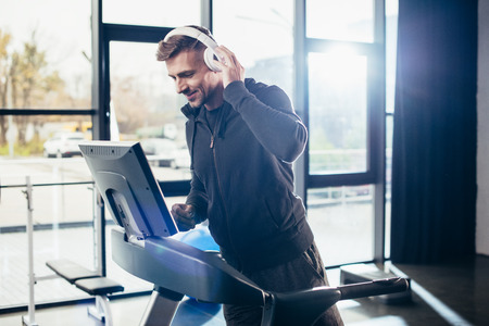 Foto per handsome sportsman in hoodie exercising on treadmill and listening to music in gym - Immagine Royalty Free