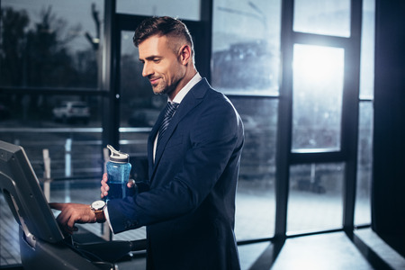 Photo pour handsome businessman in suit exercising on treadmill and holding sport bottle in gym - image libre de droit