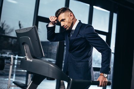 Photo pour side view of tired handsome businessman in suit exercising on treadmill in gym - image libre de droit