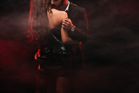 Foto de cropped view of passionate couple hugging in red smoky room - Imagen libre de derechos