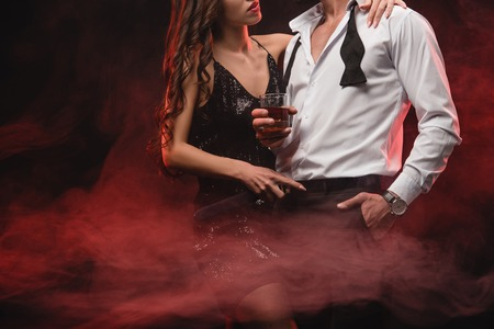 Photo for cropped view of sexy woman hugging man with glass of whiskey in red smoky room - Royalty Free Image