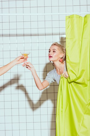 Photo for beautiful woman behind green curtain taking cocktail in shower - Royalty Free Image