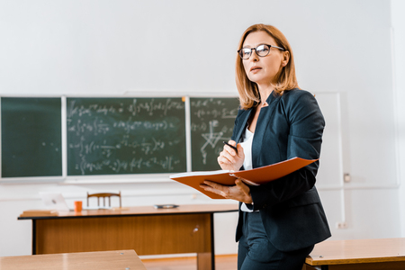 Foto de beautiful female teacher in formal wear and glasses holding notebook in classroom - Imagen libre de derechos