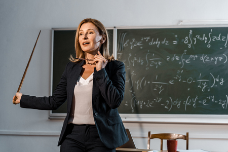 Photo pour female teacher with wooden pointer holding glasses and explaining mathematical equations in classroom - image libre de droit
