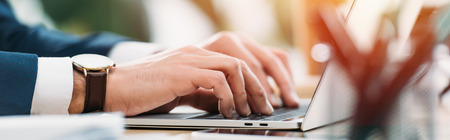 Foto de cropped view of businessman sitting at table with laptop and typing in office - Imagen libre de derechos