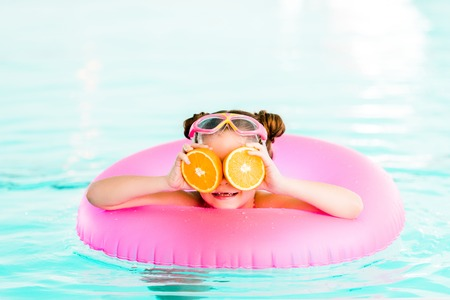 Photo pour happy child holding half oranges near eyes while  swimming with inflatable ring in swimming pool - image libre de droit