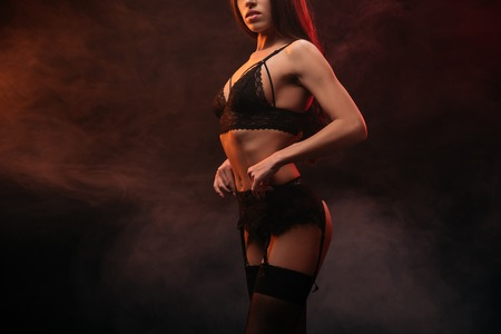 Photo for cropped view of seductive young woman in lace lingerie posing in dark smoky room - Royalty Free Image
