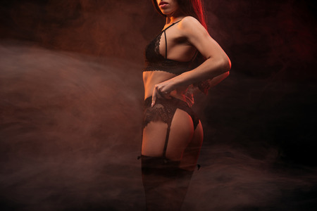 Photo for cropped view of sensual young woman in black lingerie posing in dark smoky room - Royalty Free Image