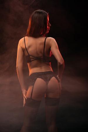 Photo for back view of sexy girl in black lingerie posing in dark smoky room - Royalty Free Image