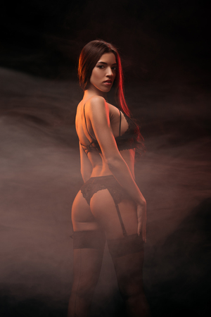 Photo for attractive sensual young woman in black erotic lingerie posing in dark smoky room - Royalty Free Image