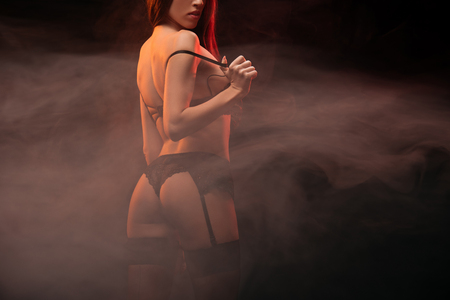 Photo for cropped view of seductive girl in black lingerie posing in dark smoky room - Royalty Free Image