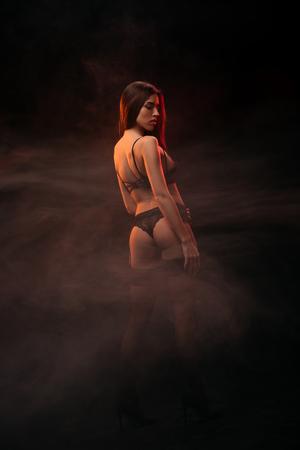 Photo for beautiful sensual young woman in black lingerie posing in dark smoky room - Royalty Free Image