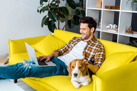 Foto de handsome laughing man using laptop on sofa with beagle dog - Imagen libre de derechos