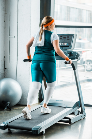 Foto per overweight girl with towel on shoulders running on treadmill in gym - Immagine Royalty Free