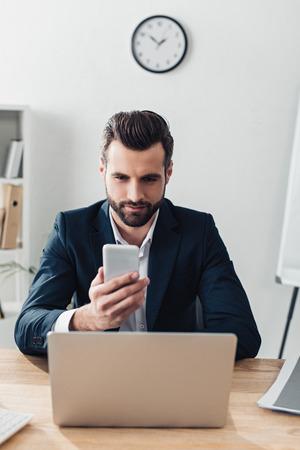 Foto de handsome advisor in suit using smartphone with laptop at workplace - Imagen libre de derechos