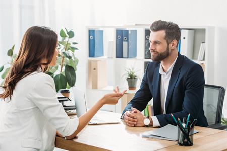 Foto de handsome advisor in suit talking with beautiful investor at office - Imagen libre de derechos