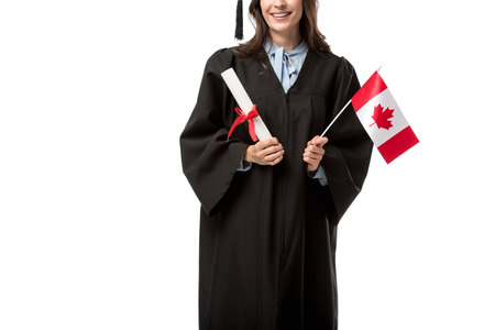 Photo pour partial view of female student in academic gown holding canadian flag and diploma isolated on white - image libre de droit