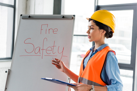 Photo pour female firefighter in helmet holding clipboard and pen while talking near white board with fire safety lettering - image libre de droit